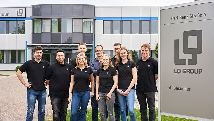 Auszubildende und Ausbilder vor dem Gebäude der LQ Group am Standort Ottmarsheim